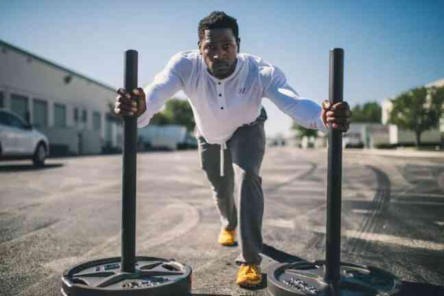 athletic man pushing sled or prowler