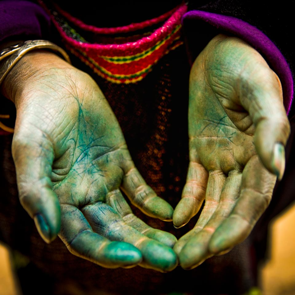 Detailed picture of the hands of a Vietnamese fabric worker with stained hands from years of working with fabric. Photography by travel photographer Steve Mason on location near the Chinese boarder in Vietnam