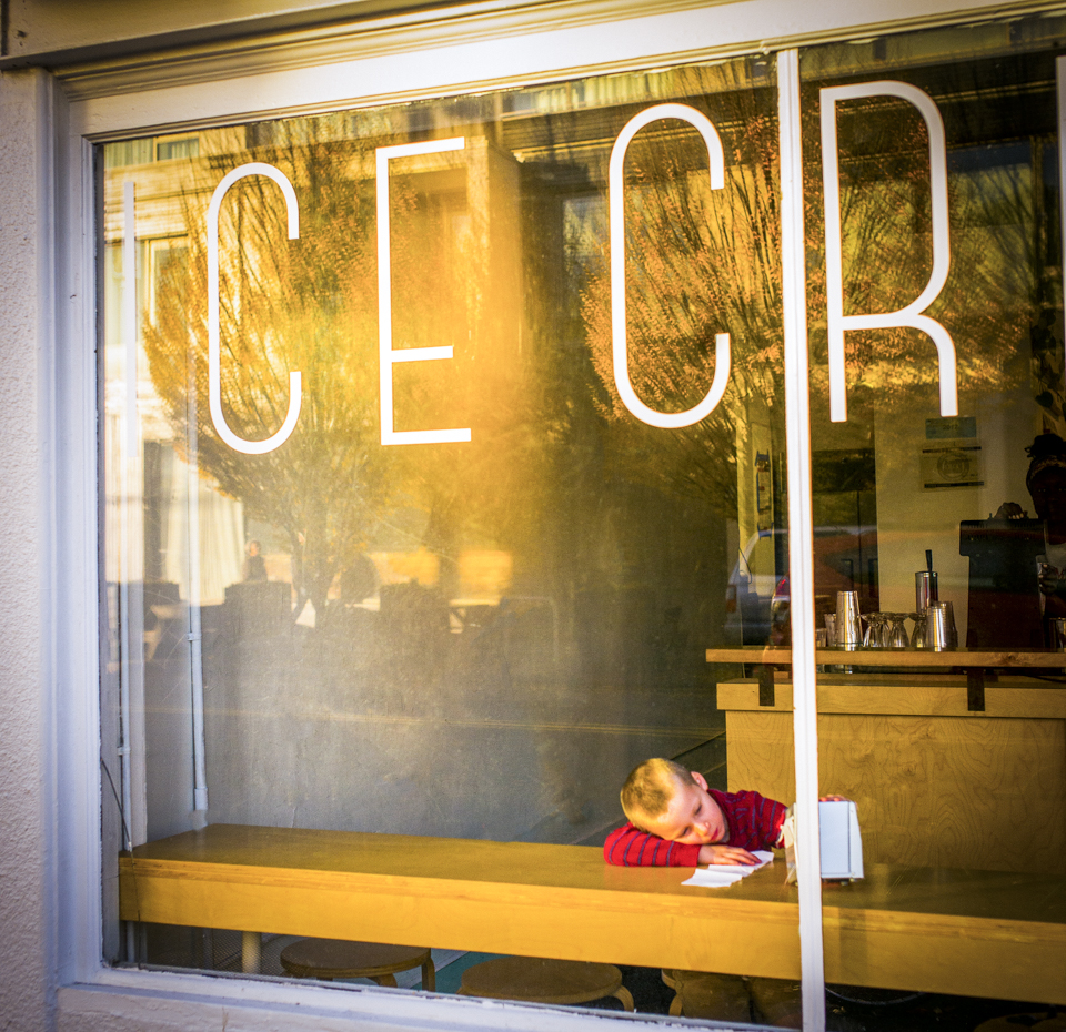 young boy waits for ice cream in the window of a ice cream shop in Portland Oregon