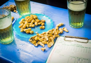 Picture of three glasses of draft beer and peanuts on blur plastic table in old city Hanoi Vietnam