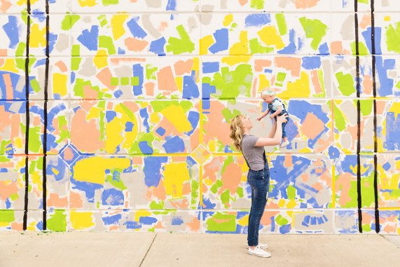 Little girl with headband and painted overalls mommy and me photo mom laughing while holding baby up in front of colorful Provo Utah mural