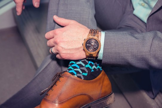 man wearing jord conway series walnut jet black unique wood watch joseph aboud gray suit steve madden shoes colorful socks legs crossed closeup