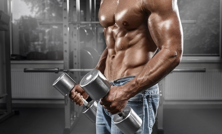 Muscular man working out in gym doing exercises with dumbbells,