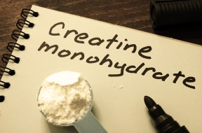 Notebook with  sign Creatine monohydrate and scoop with white po