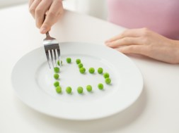 close up of woman with fork eating peas