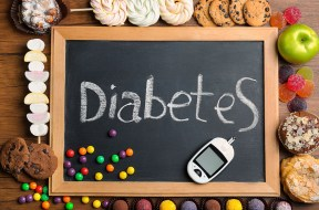 """Blackboard with word """"Diabetes"""", sweets and digital glucometer o"""