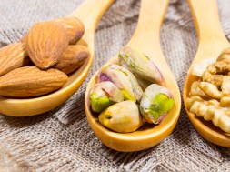 Almonds, walnuts and pistachio on a wooden spoon.