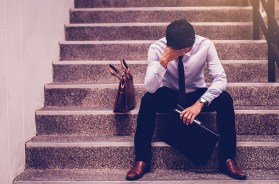stressed businessman holding portfolio sitting at stairway. disa