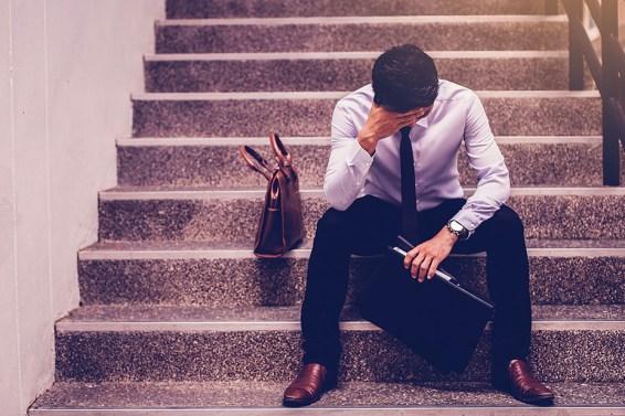 stressed businessman holding portfolio sitting at stairway. disa