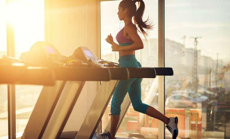 Young healthy athletic woman running on a treadmill near the sun