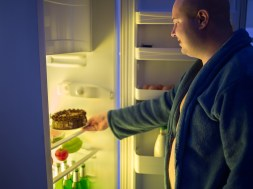 Man at night overstep and take whole chocolate cake from refrige
