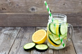 Lemon cucumber detox water in a mason jar glass with straw and s