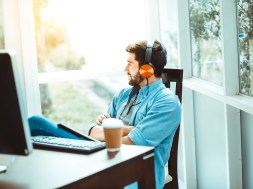 Happy Relaxed man drink coffee and Listen to music on headphones