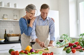 Happy old senior couple preparing vegetable salad cooking in kitchen at home.