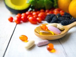 Pills and capsules in wooden spoon with fresh fruits.Vitamins an