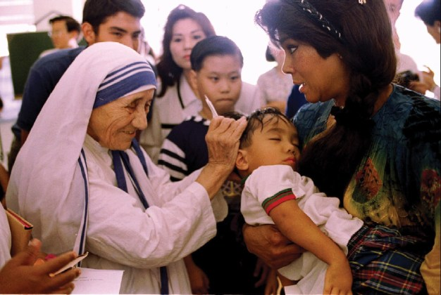 Mother Teresa blesses a sick child held by his mother October 20 at the Missionaries of Charity convent in Singapore - RTXEWYA