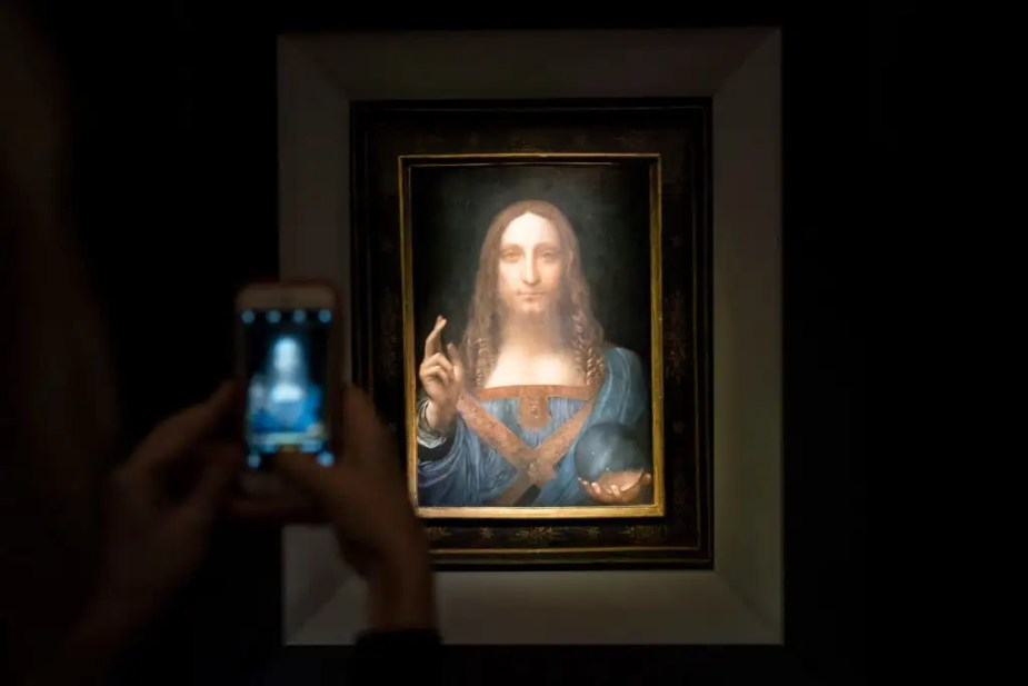 A visitor takes a photo of the painting 'Salvator Mundi' by Leonardo da Vinci at Christie's New York. (Drew Angerer/Getty Images)