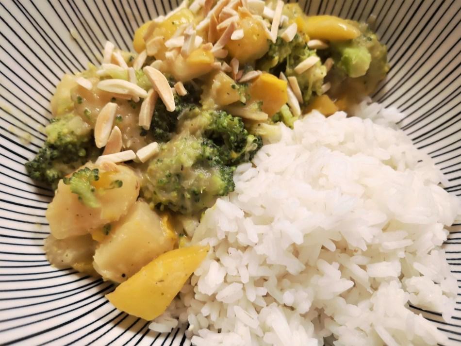 Fruchtiges Maniok Curry mit Mango & Brokkoli in einer Schüssel mit Reis angerichtet.