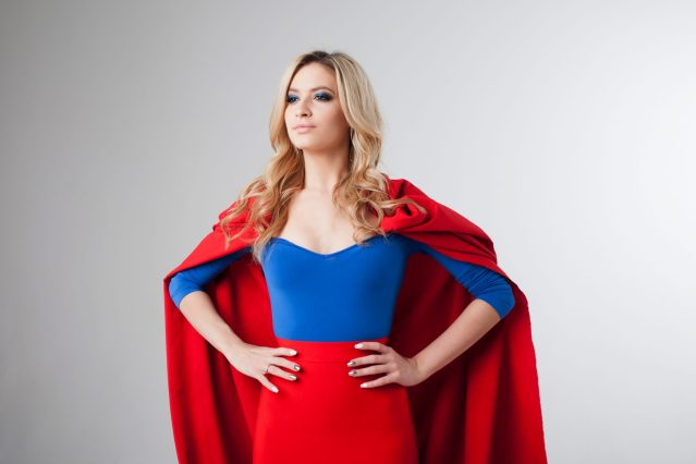 Blonde woman in a superhero costume in a confident pose with her hands on her hips.