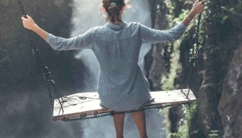 Girl in a blue shirt on a swing overlooking a steep waterfall.