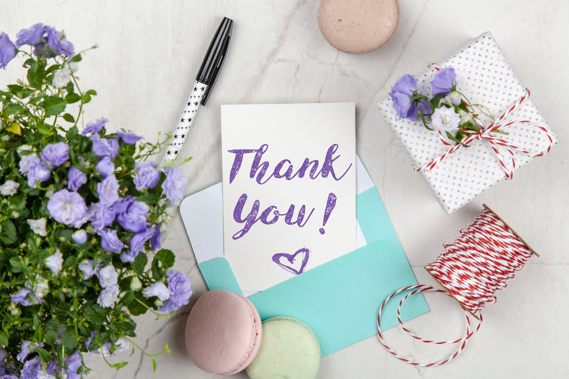 A thank you card in a blue envelope near flowers and a wrapped gift.
