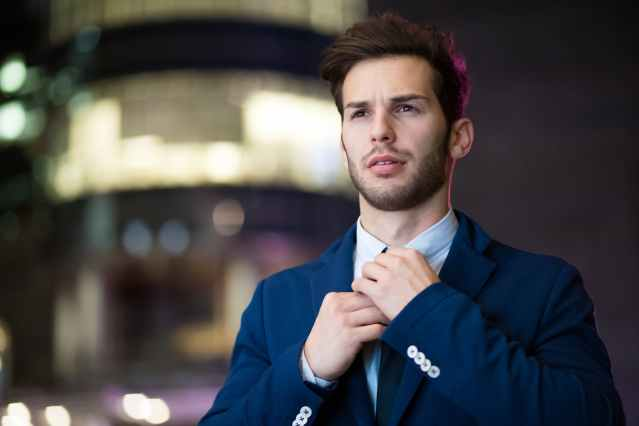 Young businessman in a blue suit adjusting his tie and feeling good about himself.
