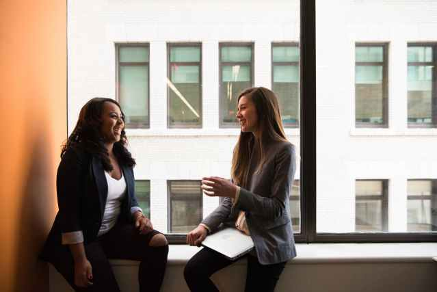 Two women coworkers sitting near full glass window ledge in the same position to show that by mimicking others you can get them to be influenced by you.