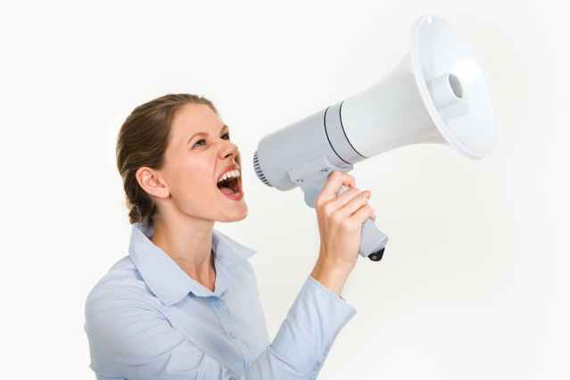 Young woman dressed in a white shirt shouting into a megaphone to illustrate that forcing your views on others is the wrong way to influence someone's decisions.