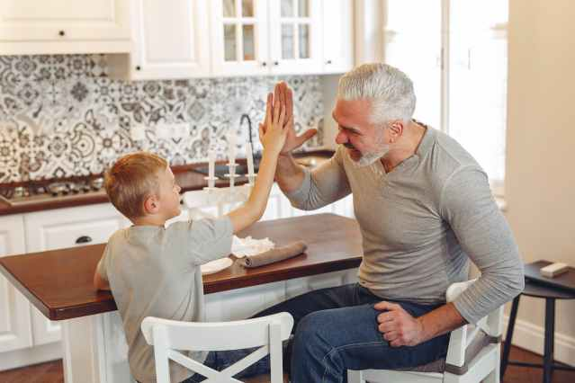 Father in gray crew neck shirt giving a high five to his son to drive behavior change while sitting at a table in the kitchen.