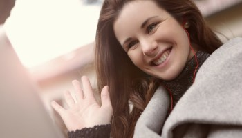 A smiling woman in a gray coat with red earphones waving her hand.