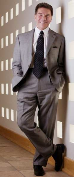 Robert Cialdini dressed in a grey suit, white shirt and black tie standing with his hands in his pockets.
