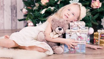 Kid holding her toys and presents in front of a Christmas tree.