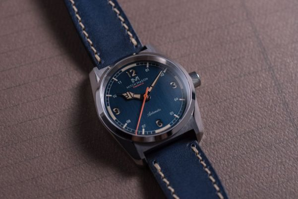Mitch Mason Chronicle Steel Blue - Case: Polished & brushed/ Rehaut: Brushed/ Dial: Sandwiched, vertical brushing with logo/ Dial colour: Blue/ Dial printing: Light grey & Orange/ Hands: Polished/ Seconds hand: Orange/ Lume: Old radium Super-LumiNova®/ Strap: Blue vegetable tanned Italian Leather.