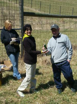 Tori Lindberg calculating times as Karen Porter presents trophy to David Ritchie.
