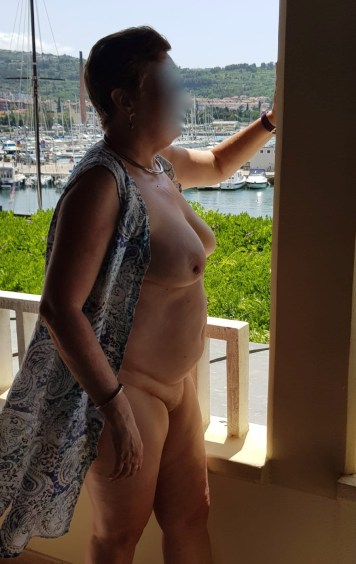 Me on the balcony in Slovenia. I have a dress on but it is undone at the front and hangs open showing my breasts, tummy and thighs.