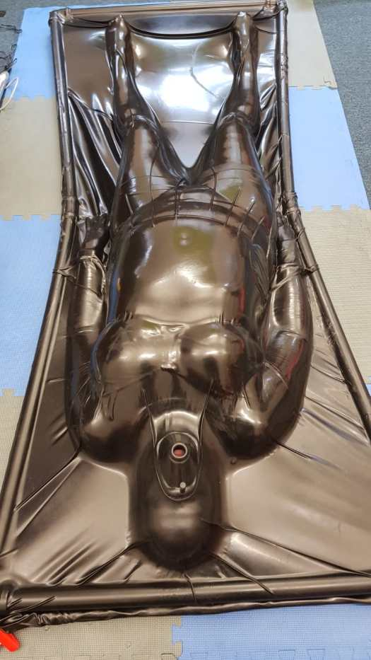 Me lying inside the vac bed completely encased in latex