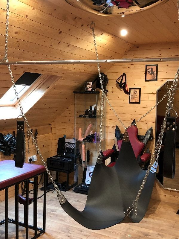 A swing, set within a BDSM dungeon room.