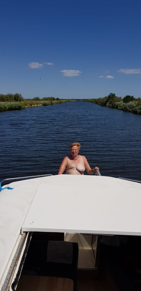 We are on a boat on the canal du rhone à Sete. I am at the back of the boat topless. I only have a left boob as I have has a mastectomy