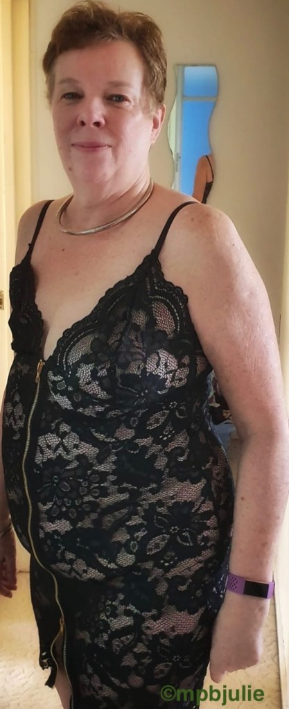 I am wearing a little black lace dress with a front fastening. Small shoulder straps.