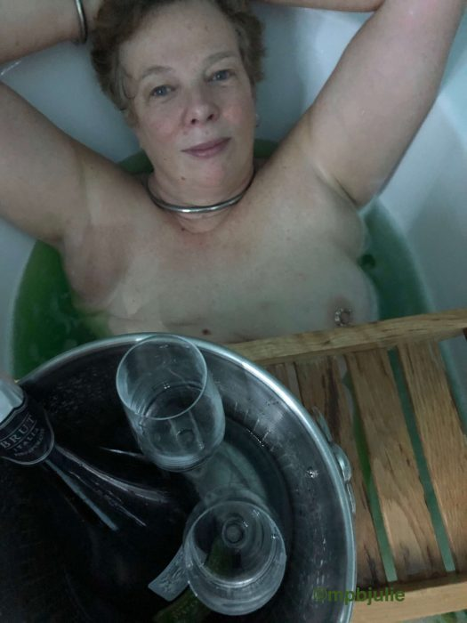 I am lying in the bath, hands behind my head. On a tray across the bath is a champagne bottle and 2 glasses in an ice bucket. They are empty.
