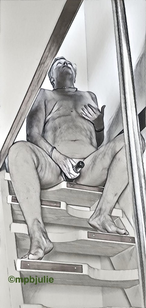 I am sitting legs spread on a narrow staircase, looking up. I am holding a vibrator between my legs.