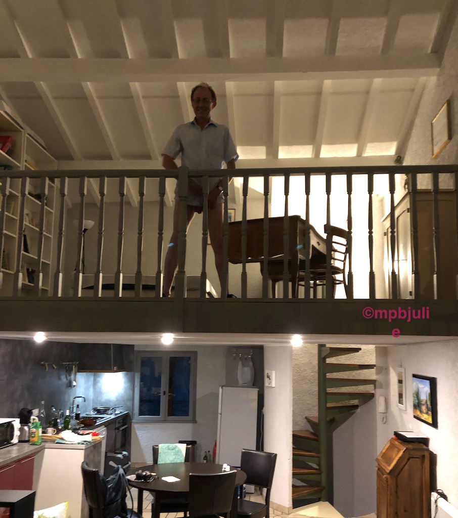 Master is standing on the mezzanine level. Un his background there are shelves, a bed, desk and chair and cabinet. Below the kitchen and dining area.