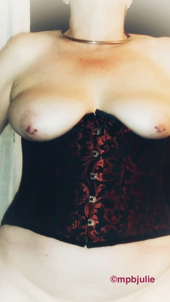 Me wearing `an under bust corset. My nipples are pierced and you can see the creases under my tummy, just above the pubes.