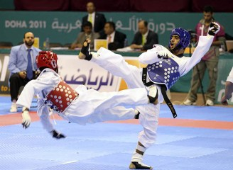 Alanazi of Saudi Arabia competes against Hussein of Sudan during their men's 54kg taekwondo match at the Arab Games in Doha