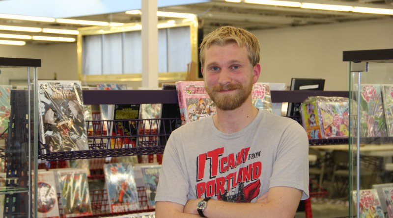 Kevin Knodell, Nerdy Stuffs' community outreach coordinator, stands in front of rows of comic books. Photo by Jessica Trondsen.