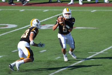 Photo Courtesy of McKenna Morin: Junior Quarterback Jon Schaub (9) does a mis-direction handoff with Junior running back Darin Hargrove (33)