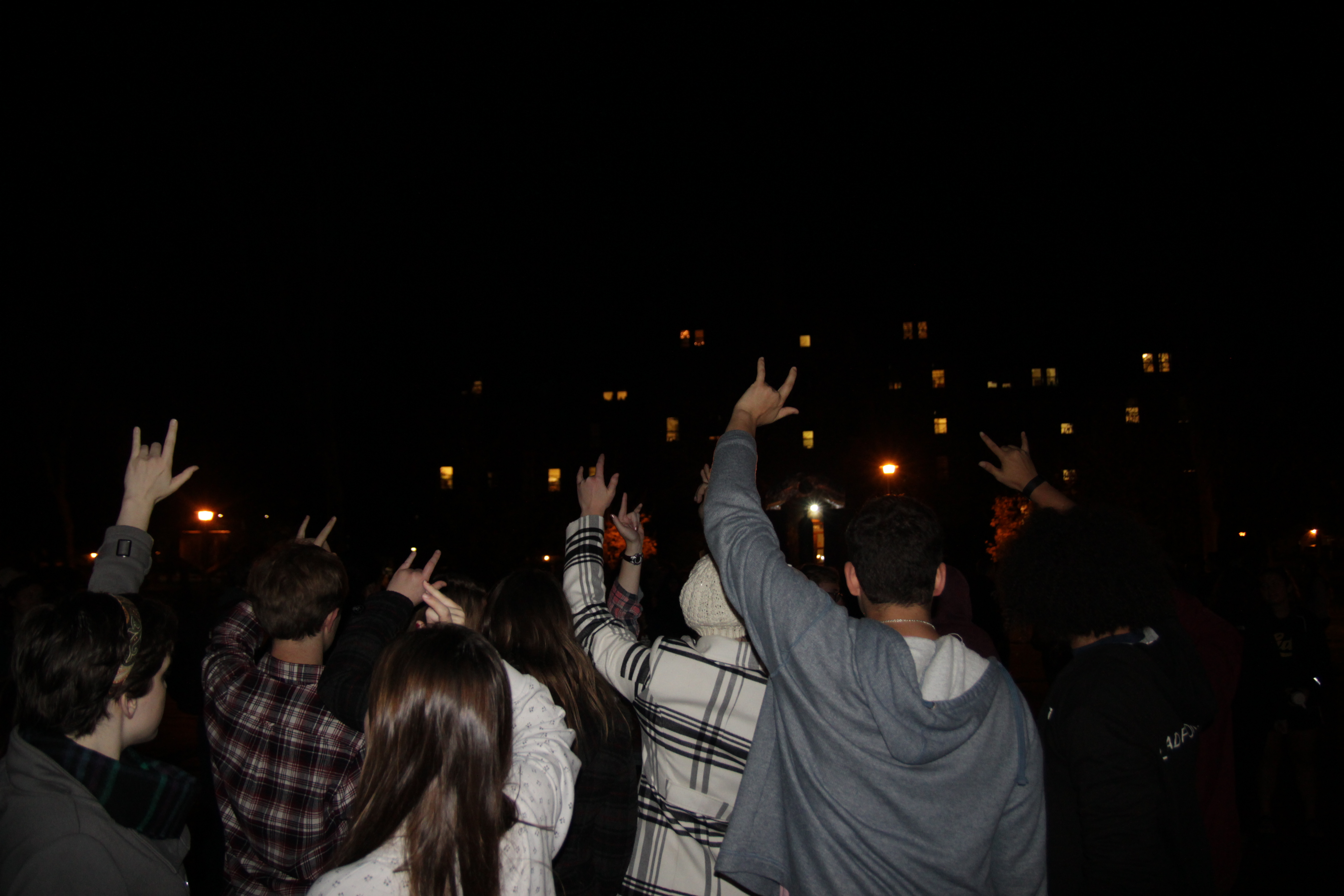 """Photo by Oliver Johnson Protesters make the American Sign Language sign for """"I love you"""" with their hands."""