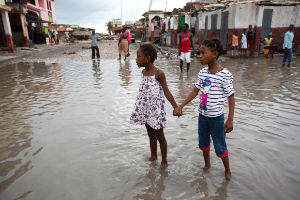 Photo courtesy of The Associated Press  Children in Les Cayes, Haiti, wade through flood brought about by Hurricane Matthew