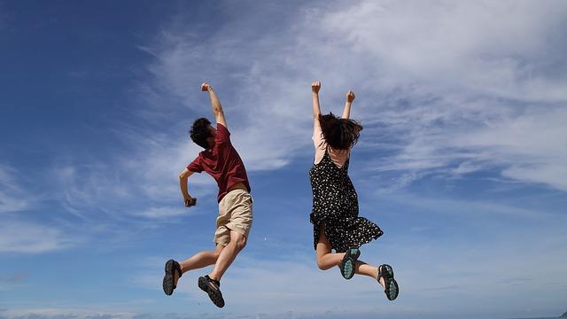 青空に向かって高くジャンプする男の子と女の子