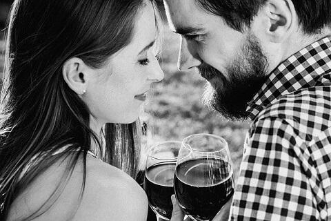 赤ワインが注がれたグラスを合わせる幸せそうなカップル